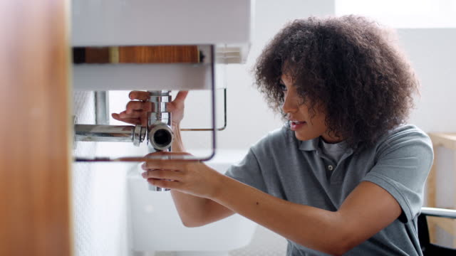 Young black female plumber sitting on the floor unscrewing the trap pipe under a bathroom sink, seen from doorway