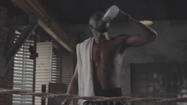 Young Black Fighter Drinking Water and Wiping off Sweat in Boxing Ring