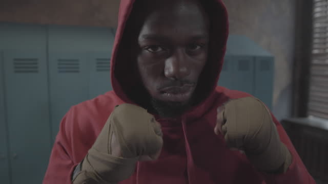 Young Black Fighter in Hoodie, with Clenched Fists Posing in Locker Room
