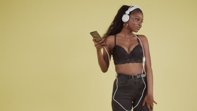 young black girl dancing to smartphone and headphones - decolleté video stock e b–roll