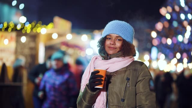Young black girl posing with hot drink on holiday market at night video