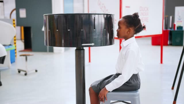 vídeos de stock e filmes b-roll de young black girl using zoetrope at a science activity centre - saia