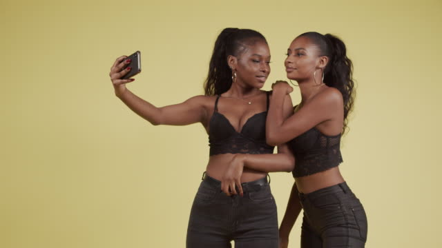 Young Black Girlfriends Posing Together For Smartphone