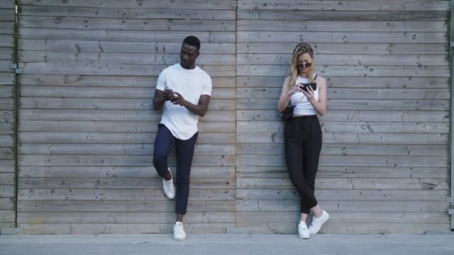 Young Black Man and Caucasian Woman Taking Selfies Leaning on Wall