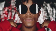 istock Young Black Man in Sunglasses Taking off Hood and Posing for Camera 1219113772