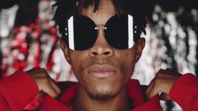 stockvideo's en b-roll-footage met jonge zwarte mens in zonnebril dat van kap en het stellen voor camera opstijgt - ontwerp