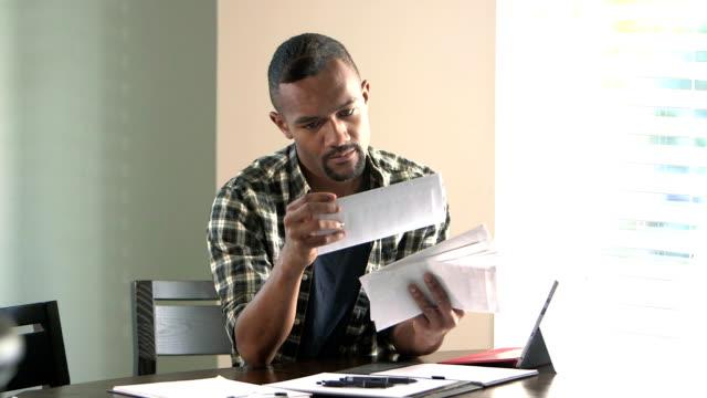vídeos de stock, filmes e b-roll de jovem negro pagando contas - e mail