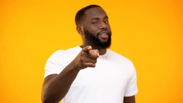 vídeos de stock e filmes b-roll de young black man pointing finger at camera and smiling against yellow background - europe points