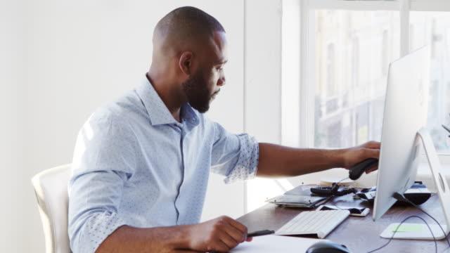 Joven negro usando el teléfono y la computadora en la oficina, cerrar - vídeo