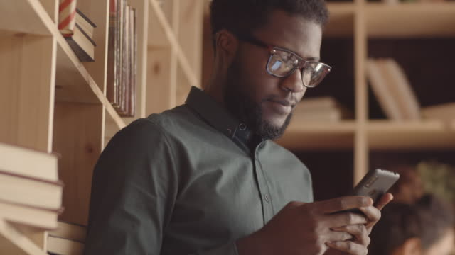 Young Black Man Using Smartphone in Cozy Book Cafe
