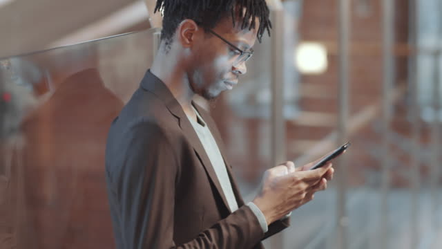 Young Black Man Using Smartphone in Office