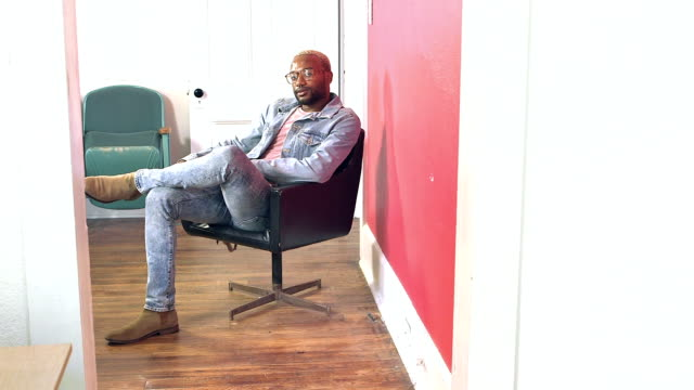 Young black man walks into room and sits in office chair A young African-American man with a nose ring, eyeglasses and dyed hair, walks into a room and sits down in an office chair. He is wearing a denim jacket and jeans. chair stock videos & royalty-free footage