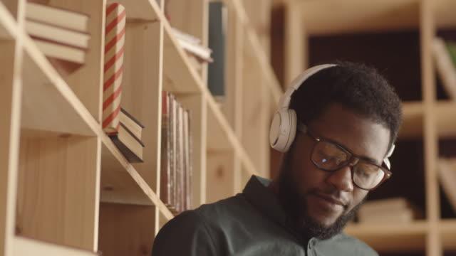 young black man with headphones using smartphone in hipster book café - cuffia attrezzatura per l'informazione video stock e b–roll