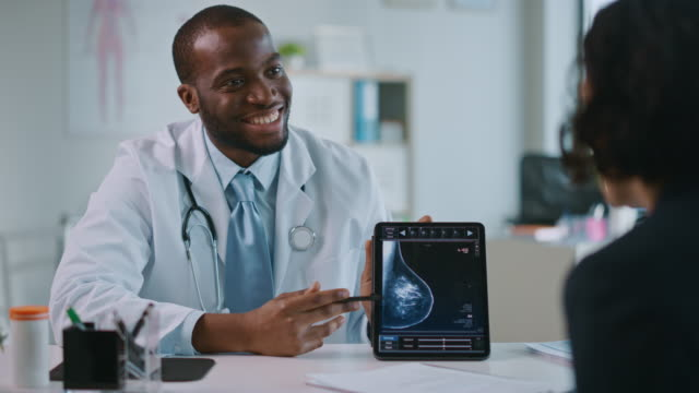 Young Black Medical Doctor Showing Mammography Test Results to a Patient on a Tablet Computer in a Health Clinic. Friendly Assistant Explains Importance of Breast Cancer Prevention Screening. Young Black Medical Doctor Showing Mammography Test Results to a Patient on a Tablet Computer in a Health Clinic. Friendly Assistant Explains Importance of Breast Cancer Prevention Screening. mammogram stock videos & royalty-free footage