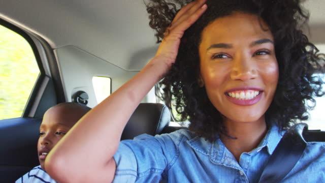 vídeos de stock, filmes e b-roll de jovem mãe negra com o menino em um carro indo em viagem - carro mulher
