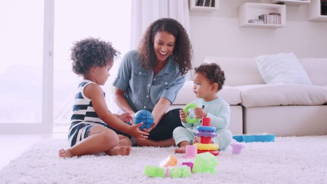 Young black mum playing with her daughter and toddler son
