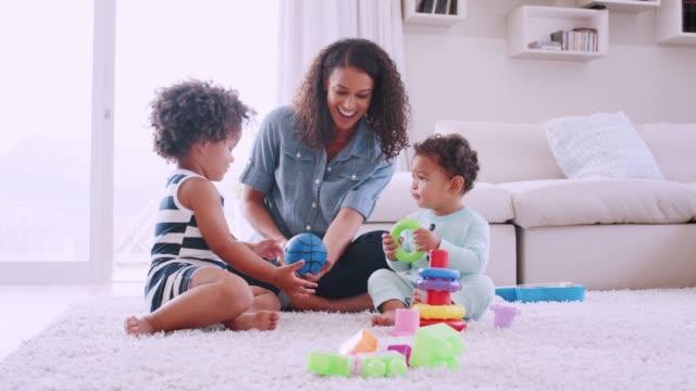 stockvideo's en b-roll-footage met jonge zwarte moeder spelen met haar dochter en peuter zoon - baby toy