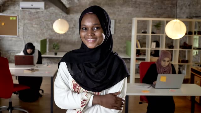 young black muslim women in hijab looking in camera, smiling, three womens working on laptop in modern office in background - nigeria video stock e b–roll