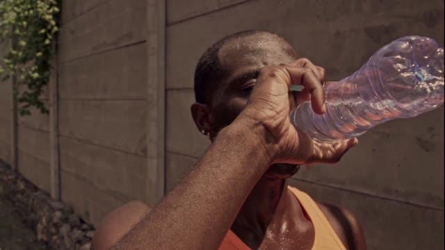 giovane corridore nero che beve acqua dopo la corsa - ritemprarsi video stock e b–roll
