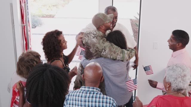 young black soldier returning to a surprise family welcome home party, elevated view - arrivo video stock e b–roll