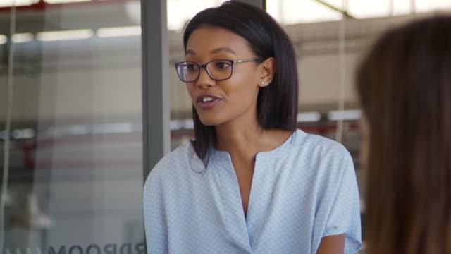 Jeune femme noire s'adressant à des collègues à la réunion, fermez vers le haut - Vidéo
