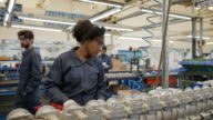 istock Young black woman assembling spare parts at a water pump factory at the production line 1206365457