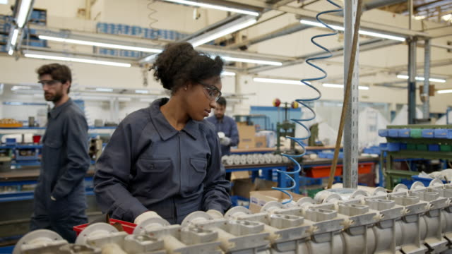 Young black woman assembling spare parts at a water pump factory at the production line