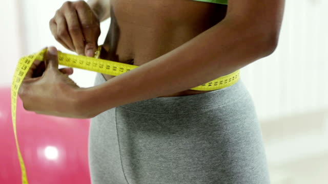 Young black woman measuring waist in gym video