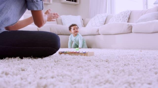 vidéos et rushes de jeune femme noire, jouer avec les tout-petits rampants, faible angle - ramper