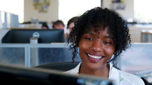 young black woman using computer in a call centre, close up - pracownik obsługi klienta filmów i materiałów b-roll