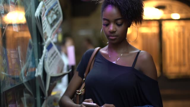 Young black woman using mobile in the city at night video