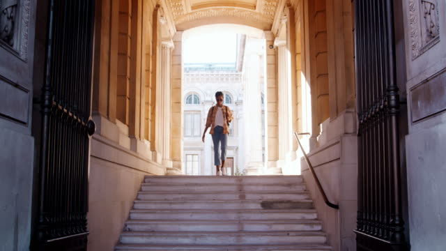 A young black woman wearing a plaid shirt and blue jeans walking down steps seen through the gateway outside a historical building, front view A young black woman wearing a plaid shirt and blue jeans walking down steps seen through the gateway outside a historical building, front view full length stock videos & royalty-free footage