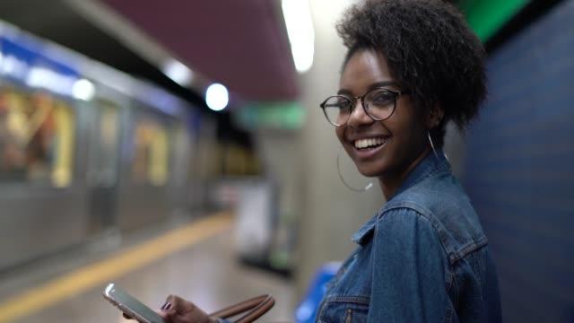 地下鉄で携帯電話を使用してアフロの髪型で若い黒人女性 - ブラジル文化点の映像素材/bロール