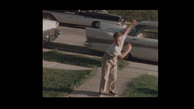 1956 Young blond boy pitches baseballs in front of vintage cars
