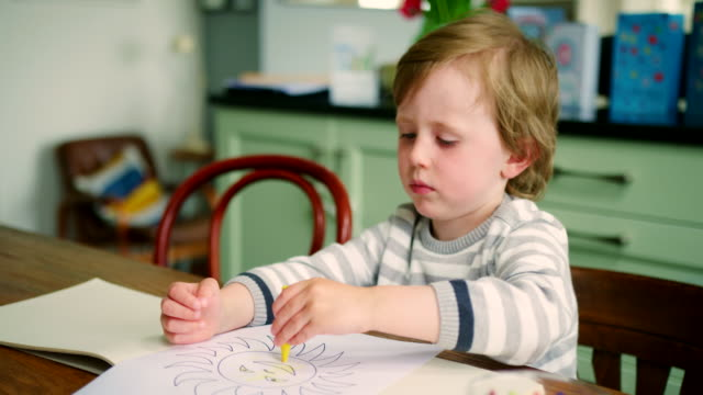 young blond boy sitting at kitchen table using crayons - matita colorata video stock e b–roll