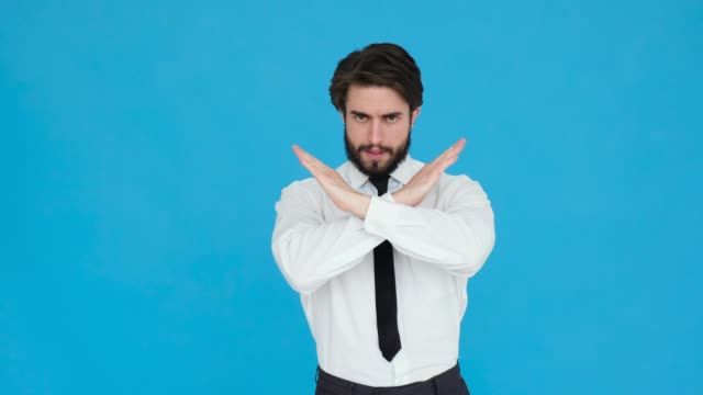 vídeos de stock e filmes b-roll de young blond businessman with beard wearing shirt over blue background rejection expression crossing arms and palms doing negative sign, angry face - crucifixo