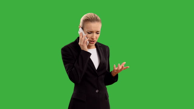 Young blond businesswoman speak for smartphone on green screen