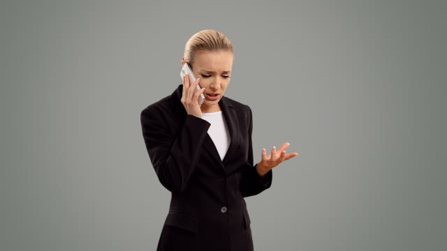 Young blond businesswoman speak for smartphone on grey background
