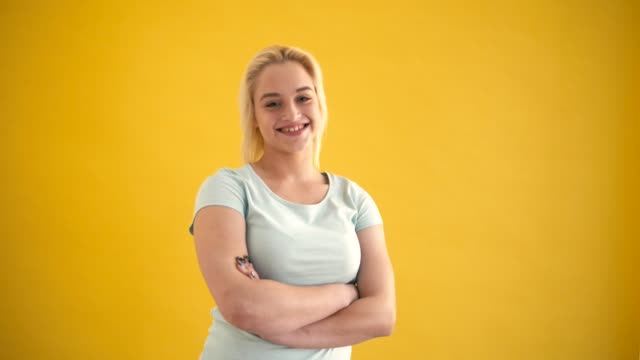 vídeos de stock e filmes b-roll de young blond caucasian plus size model posing smiling with crossing hands at yellow background - corpulento