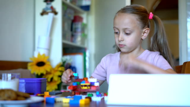 Young blond girl playing with plastic blocks at home video