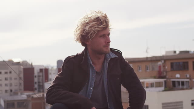 young blond male sitting at building terrace - spettinato video stock e b–roll