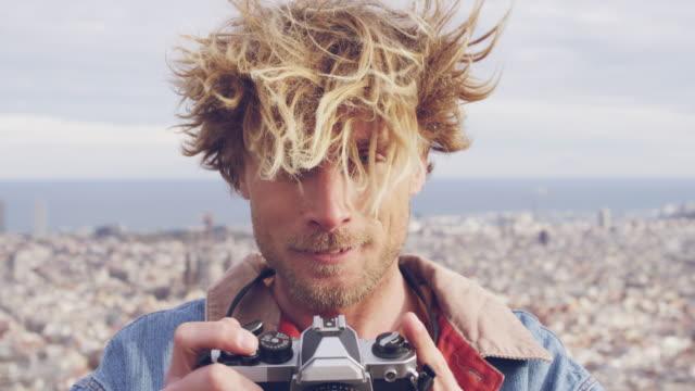 young blond male tourist photographing outdoors - młodzi mężczyźni filmów i materiałów b-roll