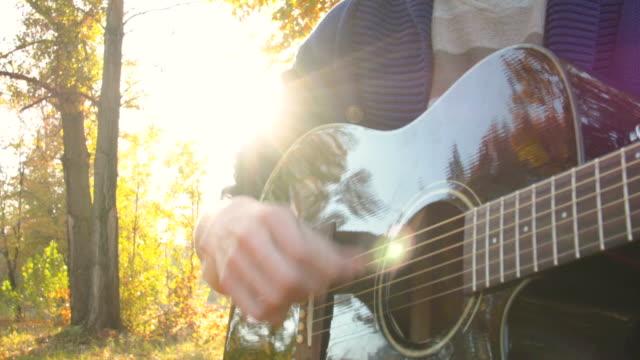 ung blond man spela akustisk gitarr i höst skog - akustisk gitarr bildbanksvideor och videomaterial från bakom kulisserna