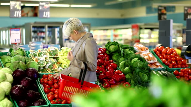 Young blond woman buying vegetable video