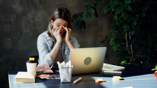 young blond woman is sitting in office working with computer. she is tired so she is touching her face and hair, rubbing her eyes, stretching her neck after long day at work. - stress emotivo video stock e b–roll
