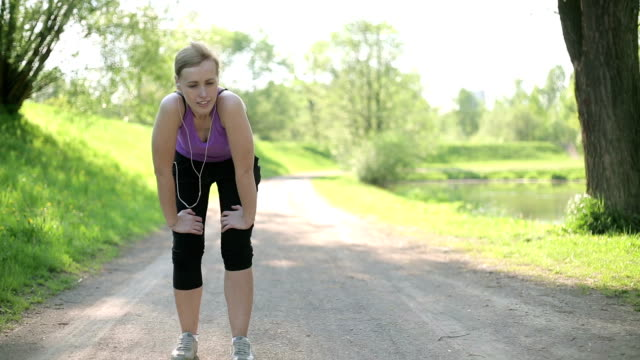 Young blond woman taking breath after jogging video