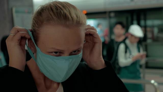 kliniğin girişinde cerrahi maske giyen genç sarışın kadın. hong kong, çin - maske stok videoları ve detay görüntü çekimi