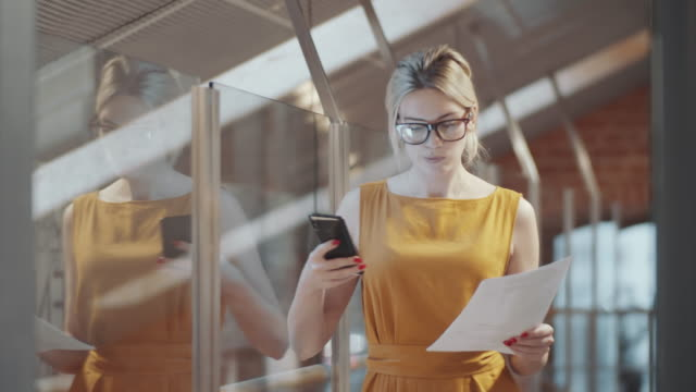 Young Blonde Businesswoman Reading Document and Using Smartphone