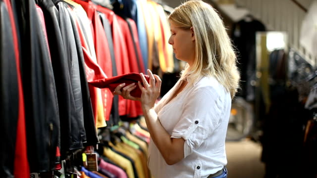 young blonde choosing leather jacket Attractive young blonde choosing leather jacket on racks in clothes store rack stock videos & royalty-free footage