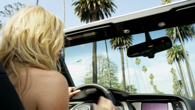 Young blonde female dancing and singing in cabriolet